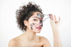 young-woman-removing-black-face-mask-against-white-background